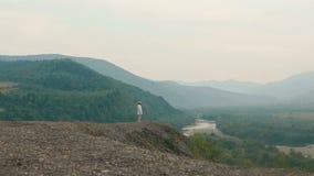 Ο γοητευτικός ταξιδιώτης απολαμβάνει το τοπίο του ποταμού περπατώντας κατά μήκος των βουνών Άποψη Copter απόθεμα βίντεο