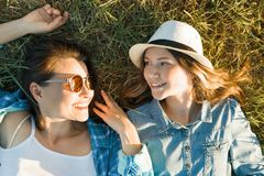 Ο γονέας και ο έφηβος, η μητέρα και η 14χρονη κόρη χαμογελούν να βρεθούν στην πράσινη χλόη επάνω από την όψη στοκ εικόνες