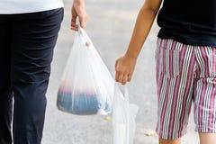 Ο γονέας και το παιδί φέρνουν τις πλαστικές τσάντες στοκ φωτογραφία με δικαίωμα ελεύθερης χρήσης