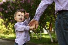 Ο γονέας κρατά το χέρι ενός μικρού παιδιού στοκ φωτογραφίες