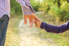 Ο γονέας που κρατά το χέρι παιδιών ` s με ένα ευτυχές υπόβαθρο στοκ εικόνες