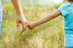 Ο γονέας που κρατά το χέρι του παιδιού με ένα ευτυχές υπόβαθρο στοκ φωτογραφία με δικαίωμα ελεύθερης χρήσης