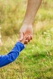 Ο γονέας που κρατά το χέρι του παιδιού με ένα ευτυχές υπόβαθρο στοκ εικόνες