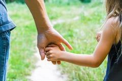 Ο γονέας που κρατά το χέρι του παιδιού με ένα ευτυχές υπόβαθρο στοκ φωτογραφία