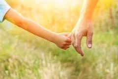 Ο γονέας που κρατά το χέρι του παιδιού με ένα ευτυχές υπόβαθρο στοκ εικόνες με δικαίωμα ελεύθερης χρήσης