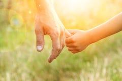 Ο γονέας που κρατά το χέρι του παιδιού με ένα ευτυχές υπόβαθρο στοκ φωτογραφίες
