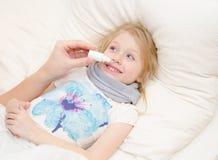 Ο γονέας στάζει το φάρμακο στη μύτη του μικρού κοριτσιού Στοκ εικόνες με δικαίωμα ελεύθερης χρήσης