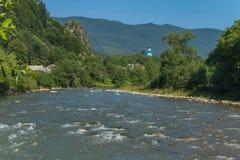 Ο γρήγορος ποταμός βουνών στα πλαίσια της μπλε κορυφής της εκκλησίας εκκλησιών, των μικρών σπιτιών και των δύσκολων βουνών Στοκ φωτογραφία με δικαίωμα ελεύθερης χρήσης