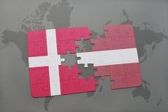 ο γρίφος με τη εθνική σημαία της Δανίας και η Λετονία σε έναν κόσμο χαρτογραφούν το υπόβαθρο Στοκ φωτογραφία με δικαίωμα ελεύθερης χρήσης