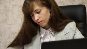 Ο γραμματέας γράφει τη μάνδρα στο σημειωματάριο η συνεδρίαση κοριτσιών στην καρέκλα στην αρχή στον υπολογιστή και παίρνει τις σημ απόθεμα βίντεο