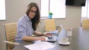 Ο γραμματέας γυναικών εργάζεται, χρησιμοποιώντας το lap-top και τα έγγραφα καθμένος στον πίνακα στην επιχείρηση απόθεμα βίντεο