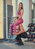 Ο γυμνός νέος μυϊκός τύπος κρατά ένα κορίτσι στους ώμους του και κάνει τις στάσεις οκλαδόν σε μια γυμναστική Στοκ Εικόνες