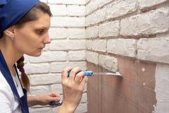 Ο γυψαδόρος κοριτσιών βάζει στον τοίχο με τη μίμησης πλινθοδομή ασβεστοκονιάματος στοκ εικόνες με δικαίωμα ελεύθερης χρήσης