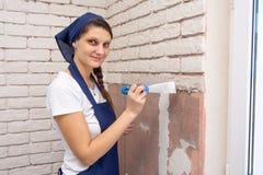 Ο γυψαδόρος κοριτσιών κάνει την πλινθοδομή στον τοίχο και εξετασμένος το πλαίσιο στοκ εικόνες