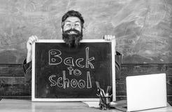 Ο δάσκαλος ή ο διευθυντής σχολείου καλωσορίζει με την επιγραφή πινάκων πίσω στο σχολείο Ευπρόσδεκτη πλάτη Αρχή του νέου σχολείου στοκ εικόνες