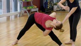 Ο δάσκαλος γιόγκας βοηθά μια γυναίκα για να κάνει ένα τρίγωνο να θέσει στη γυμναστική απόθεμα βίντεο