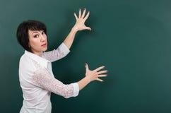 Ο δάσκαλος γυναικών παρουσιάζει σε έναν πίνακα τίποτα, το κενό διάστημα για το κείμενο και γραφική παράσταση, πράσινο υπόβαθρο, π στοκ φωτογραφία