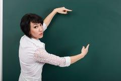 Ο δάσκαλος γυναικών παρουσιάζει σε έναν πίνακα τίποτα, το κενό διάστημα για το κείμενο και γραφική παράσταση, πράσινο υπόβαθρο, π στοκ εικόνες με δικαίωμα ελεύθερης χρήσης