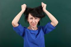 Ο δάσκαλος γυναικών στην τοποθέτηση πίεσης στο υπόβαθρο πινάκων κιμωλίας, αγγίζει την τρίχα της Στοκ Εικόνες