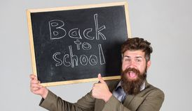 Ο δάσκαλος διαφημίζει πίσω στη μελέτη, αρχίζει το σχολικό έτος Προσκαλέστε για να γιορταστεί η ημέρα της γνώσης Γενειοφόρες στάσε στοκ φωτογραφία