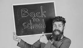 Ο δάσκαλος διαφημίζει πίσω στη μελέτη, αρχίζει το σχολικό έτος Προσκαλέστε για να γιορταστεί η ημέρα της γνώσης Γενειοφόρες στάσε στοκ εικόνες