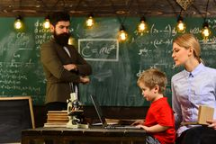 Ο δάσκαλος κάθεται στον πίνακα στο σπουδαστή τάξεων, καθηγητή και σχολείων στην τάξη σε ένα σχολείο, όμορφος δάσκαλος Στοκ εικόνα με δικαίωμα ελεύθερης χρήσης