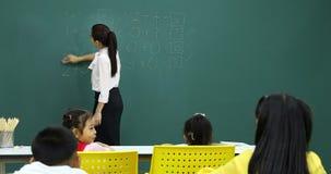 Ο δάσκαλος καθαρίζει τον πίνακα έχει math τα προβλήματα απόθεμα βίντεο