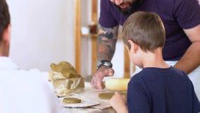 Ο δάσκαλος μαθαίνει το μικρό παιδί πώς στο sculpt από τον άργιλο απόθεμα βίντεο