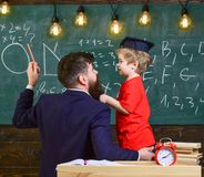 Ο δάσκαλος με τη γενειάδα, πατέρας διδάσκει λίγο γιο στην τάξη, πίνακας κιμωλίας στο υπόβαθρο Διδακτική έννοια συνομιλίας στοκ εικόνες με δικαίωμα ελεύθερης χρήσης