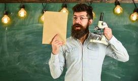 Ο δάσκαλος της βιολογίας eyeglasses κρατά το βιβλίο και το μικροσκόπιο Άτομο με τη γενειάδα στο έκπληκτο πρόσωπο στην τάξη bipeds στοκ φωτογραφίες