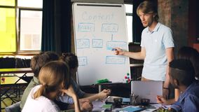 Ο δημιουργικός διευθυντής χρησιμοποιεί whiteboard στην επιχειρησιακή συνεδρίαση που δείχνει στο διάγραμμα και που μιλά ενώ η ομάδ απόθεμα βίντεο