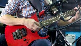 Ο δημιουργικός μουσικός ατόμων στο στούντιο εργάζεται με το παιχνίδι, το τραγούδι και την καταγραφή της κιθάρας με το σημειωματάρ απόθεμα βίντεο
