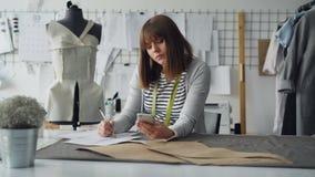 Ο δημιουργικός σχεδιαστής ιματισμού εξετάζει το smartphone και σύρει το σκίτσο εργαζόμενος στο σύγχρονο κατάστημα ραφτών στο ράψι φιλμ μικρού μήκους