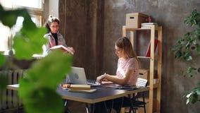 Ο δημιουργικός σχεδιαστής σύρει τις εικόνες στο σημειωματάριο ενώ ο συνάδελφός της προέρχεται, παίρνοντας το φάκελλο από το ξύλιν απόθεμα βίντεο