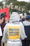Ο διαμαρτυρόμενος με ένα σημάδι που διαβάζει προστατεύει την που έχουν μεταναστεύσει νεολαία μας Στοκ φωτογραφία με δικαίωμα ελεύθερης χρήσης