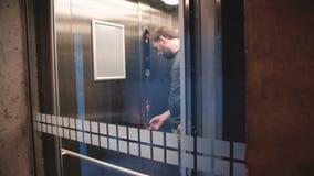 Ο διαφανής ανελκυστήρας φθάνει στο πάτωμα, νεολαίες το τονισμένο που σοβαρό ευρωπαϊκό άτομο εισάγει και οδηγά επάνω, άποψη μέσω τ φιλμ μικρού μήκους