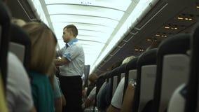 Ο διαχειριστής στο αεροπλάνο παρουσιάζει κανόνες ασφάλειας φιλμ μικρού μήκους