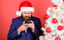 Ο διευθυντής συγχαίρει τους συναδέλφους on-line Διαβάστε το χαιρετισμό Χριστουγέννων Ατόμων γενειοφόρος hipster λαβή καπέλων κοστ στοκ φωτογραφία