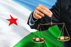 Ο δικαστής κρατά τις χρυσές κλίμακες της δικαιοσύνης με το κυματίζοντας υπόβαθρο σημαιών του Τζιμπουτί Θέμα ισότητας και νομική έ στοκ εικόνες