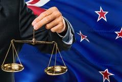 Ο δικαστής κρατά τις χρυσές κλίμακες της δικαιοσύνης με το κυματίζοντας υπόβαθρο σημαιών της Νέας Ζηλανδίας Θέμα ισότητας και νομ διανυσματική απεικόνιση