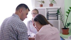 Ο διορισμός γιατρών, θηλυκός παθολόγος λέει τις κακές ειδήσεις για μια υγεία γυναικών στο παντρεμένο ζευγάρι σε ένα ιατρικό γραφε απόθεμα βίντεο