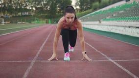 Ο δρομέας κοριτσιών υποστηρίζει μια θέση στην έναρξη πριν από τη φυλή αθλητής στην αθλητική ενδυμασία και τα έξυπνα ρολόγια απόθεμα βίντεο