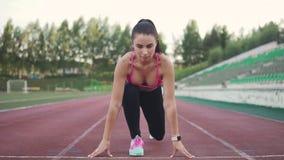 Ο δρομέας κοριτσιών υποστηρίζει μια θέση στην έναρξη πριν από τη φυλή αθλητής στην αθλητική ενδυμασία και τα έξυπνα ρολόγια φιλμ μικρού μήκους