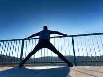 Ο δρομέας πρωινού στις ψηλές μαύρες περικνημίδες κάνει το τέντωμα σωμάτων στην πορεία γεφυρών Υπαίθρια άσκηση Στοκ εικόνες με δικαίωμα ελεύθερης χρήσης