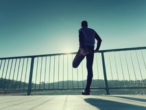 Ο δρομέας πρωινού στις ψηλές μαύρες περικνημίδες κάνει το τέντωμα σωμάτων στην πορεία γεφυρών Υπαίθρια άσκηση Στοκ εικόνα με δικαίωμα ελεύθερης χρήσης