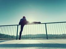 Ο δρομέας στις μαύρες περικνημίδες κάνει το τέντωμα σωμάτων στην πορεία γεφυρών Ο ήλιος περιγράφει το σώμα ατόμων Στοκ φωτογραφία με δικαίωμα ελεύθερης χρήσης