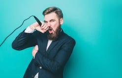 Ο δροσερός τύπος τραγουδά Επιθυμεί να τραγουδήσει στο μικρόφωνο Το άτομο στη κάμερα με μια σοβαρή θέα Απομονωμένος στο μπλε Στοκ Εικόνες