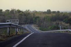 Ο δρόμος έχει μια κίτρινη γραμμή και υπάρχει ένα προειδοποιητικό σημάδι στην απότομη αριστερή πλευρά κάτω από τον στοκ εικόνες με δικαίωμα ελεύθερης χρήσης