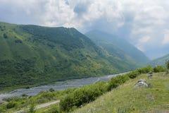 Ο δρόμος κατά τη θερινή άποψη Genaldon φαραγγιών και ποταμών Karmadon Βόρεια Οσετία, Ρωσία βουνά Καύκασου Στοκ Φωτογραφία