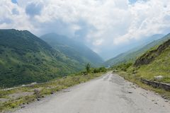 Ο δρόμος κατά τη θερινή άποψη Genaldon φαραγγιών και ποταμών Karmadon Βόρεια Οσετία, Ρωσία βουνά Καύκασου Στοκ εικόνες με δικαίωμα ελεύθερης χρήσης